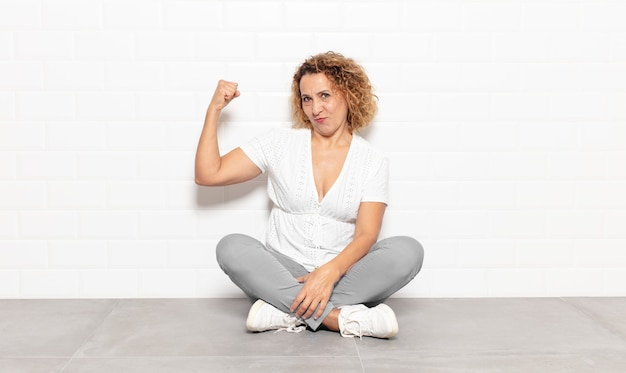 중년 여성이 행복하고 만족스럽고 강력하며 유연한 착용감과 근육질 이두근을 느끼고 체육관 후 강하게 보입니다.