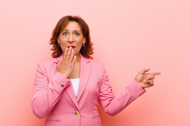Женщина среднего возраста чувствует себя счастливой, потрясенной и удивленной, прикрывая рот рукой и указывая на боковое пространство копии на розовой стене