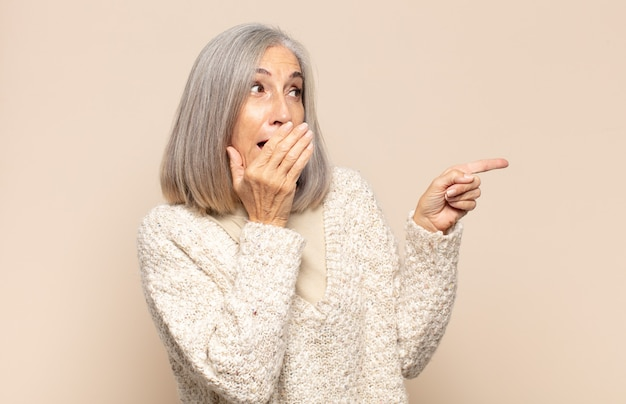 Middle age woman feeling happy, shocked and surprised, covering mouth with hand and pointing to lateral copy space