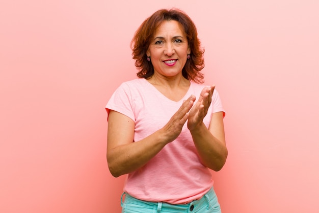 Middle age woman feeling happy and successful, smiling and clapping hands, saying congratulations with an applause against pink wall