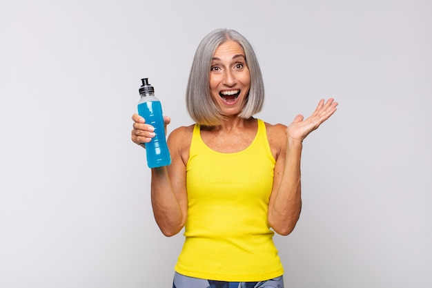 幸せ、驚き、陽気を感じ、前向きな姿勢で笑い、解決策やアイデアを実現する中年女性。フィットネスコンセプト