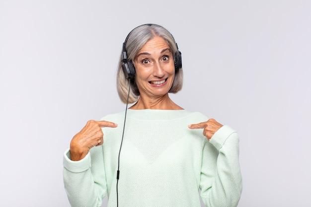 Женщина среднего возраста чувствует себя счастливой, удивленной и гордой, указывая на себя взволнованным, изумленным взглядом. музыкальная концепция