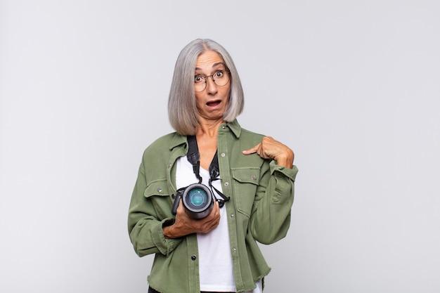 幸せ、驚き、誇りを感じ、興奮した驚きの表情で自分を指さしている中年女性。写真家のコンセプト
