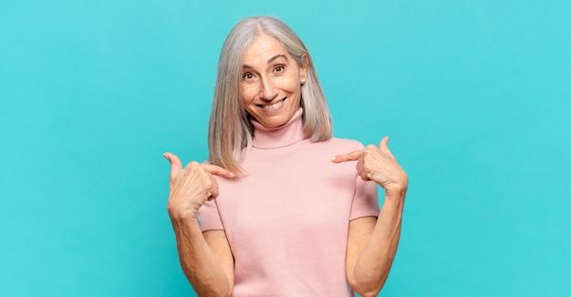 Женщина среднего возраста чувствует себя счастливой, удивленной и гордой, указывая на себя взволнованным, изумленным взглядом