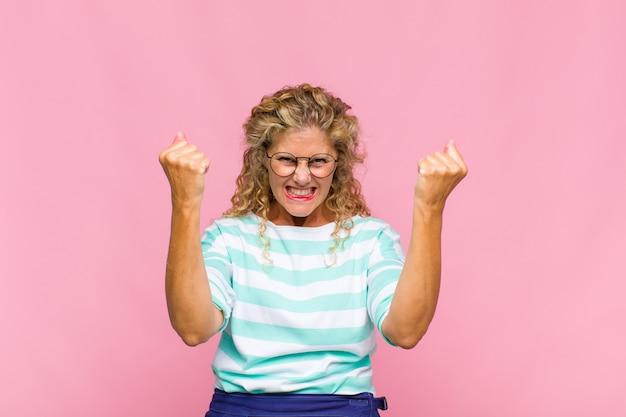 Женщина среднего возраста чувствует себя счастливой, удивленной и гордой, кричит и празднует успех с широкой улыбкой