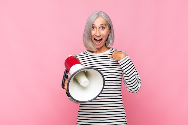 Middle age woman feeling happy, surprised and proud, pointing to self with an excited, amazed look with a megaphone