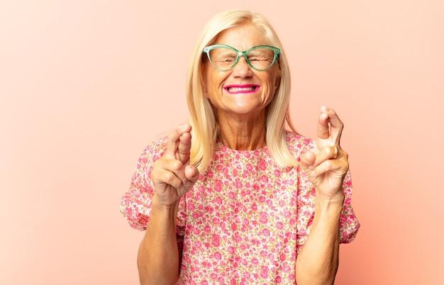 指を交差させて希望を感じている中年女性