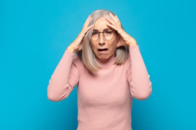恐怖とショックを感じ、手を頭に上げ、間違いでパニックに陥る中年女性
