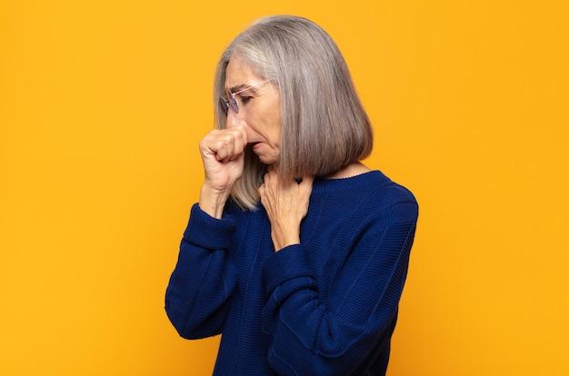 중년 여성이 인후통과 독감 증상으로 아파서 입을 덮고 기침