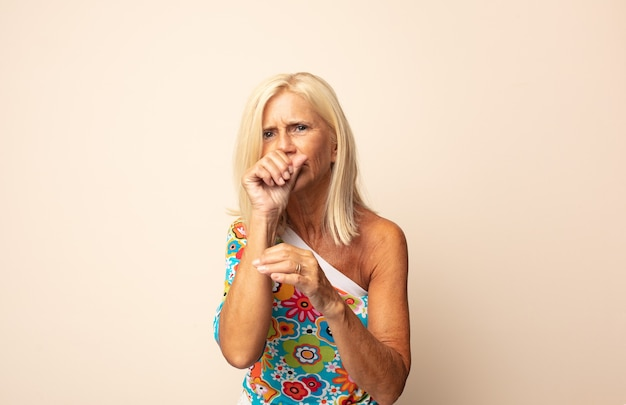 喉の痛みとインフルエンザの症状で気分が悪い中年女性