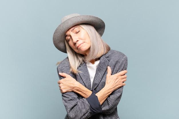 Женщина среднего возраста чувствует себя влюбленной, улыбается, обнимает и обнимает себя, остается одинокой, эгоистичной и эгоцентричной.