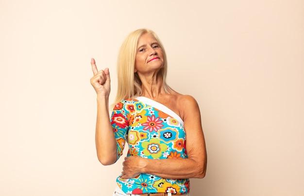 '유레카'라고 말하며 좋은 아이디어를 깨닫고 자랑스럽게 손가락을 들고 천재처럼 느껴지는 중년 여성