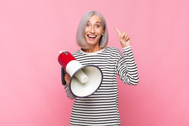 Женщина среднего возраста чувствует себя счастливым и взволнованным гением после реализации идеи