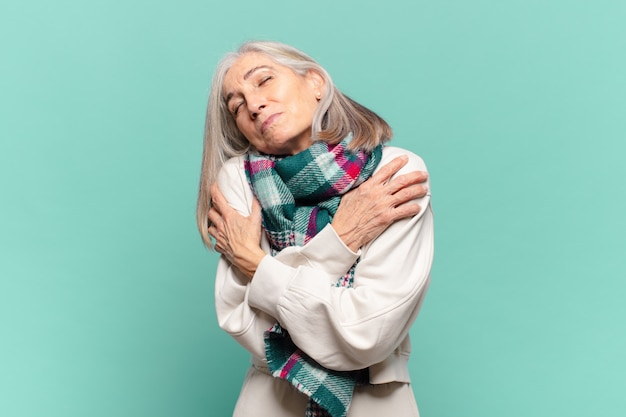 Middle age woman feeling in love, smiling, cuddling and hugging self, staying single
