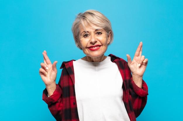 Женщина среднего возраста нервничает и полна надежды, скрещивает пальцы, молится и надеется на удачу