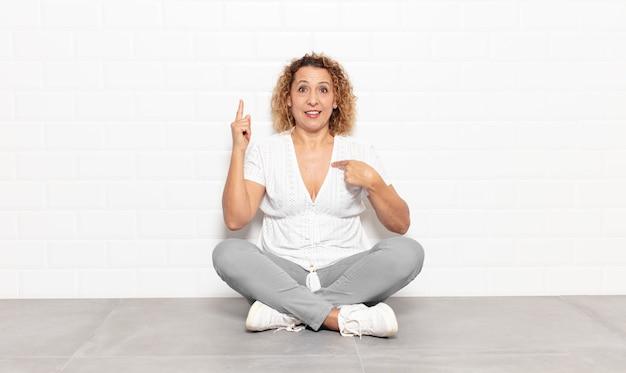 Женщина среднего возраста, гордая и удивленная, уверенно указывая на себя, чувствуя себя успешным номером один