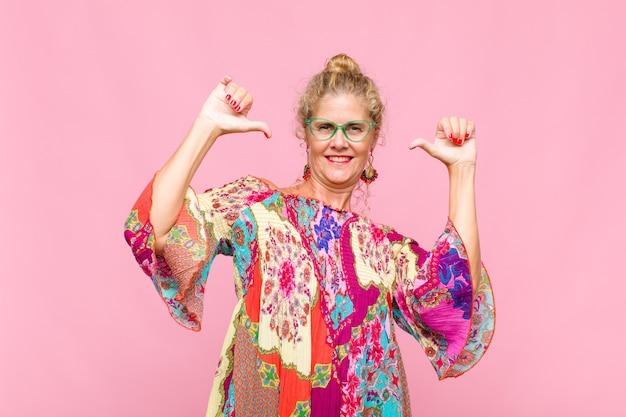 중년 여성이 자랑스럽고 거만하며 자신감이 넘치고 만족스럽고 성공 해 보이며 자신을 가리키는