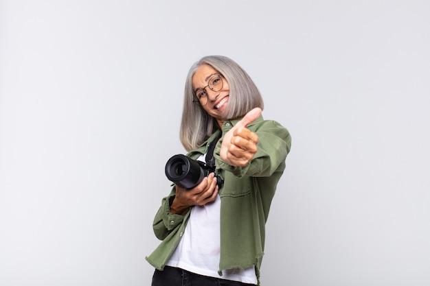 Женщина среднего возраста чувствует себя гордой, беззаботной, уверенной и счастливой, позитивно улыбается, подняв палец вверх. концепция фотографа