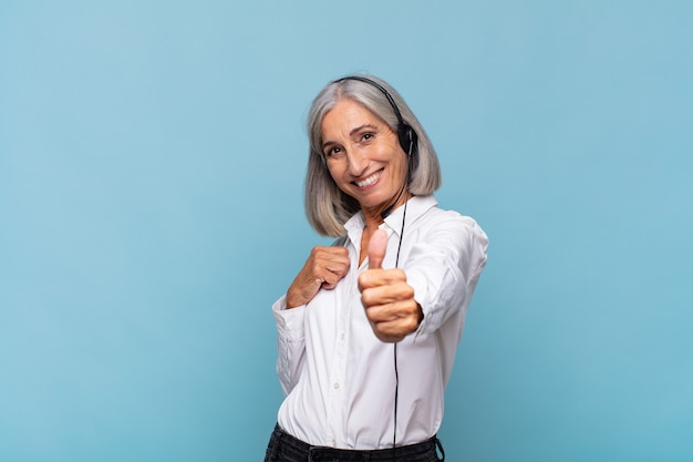 Женщина среднего возраста чувствует себя гордой, беззаботной, уверенной и счастливой, позитивно улыбается, подняв палец вверх. концепция телемаркетинга
