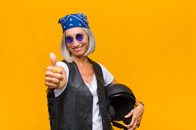 Женщина среднего возраста чувствует себя гордой, беззаботной, уверенной и счастливой, позитивно улыбается и показывает палец вверх
