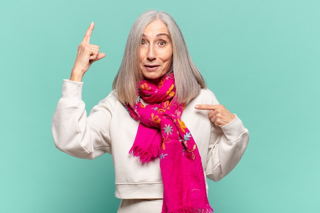 Middle age woman feeling proud and surprised, pointing to self confidently, feeling like successful number one