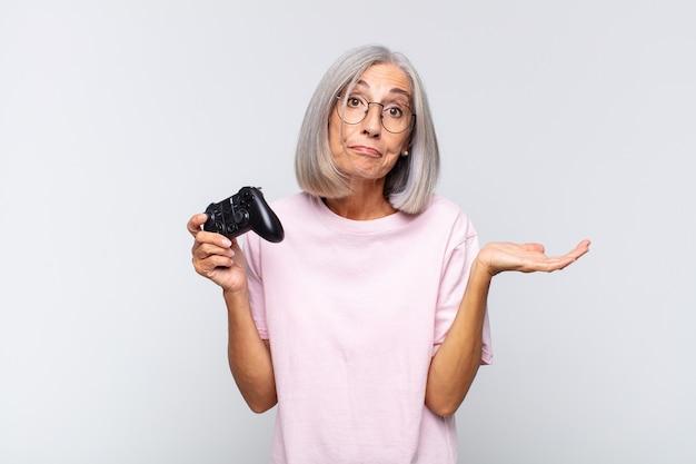 중년 여성은 의아해하고 혼란스럽고 의심스럽고 가중치를 주거나 재미있는 표현으로 다른 옵션을 선택합니다. 콘솔 개념 재생