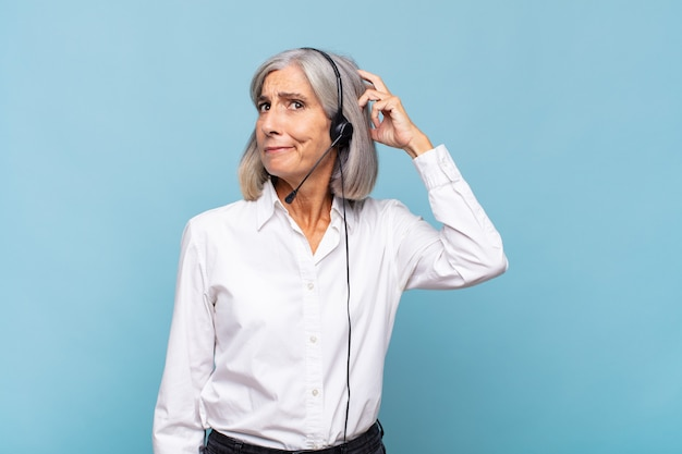 Женщина среднего возраста чувствует себя озадаченной и сбитой с толку, почесывает голову и смотрит в сторону. концепция телемаркетинга