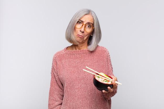 Женщина среднего возраста чувствует себя грустной и плаксивой с несчастным видом, плачет с негативным и разочарованным отношением к концепции азиатской кухни