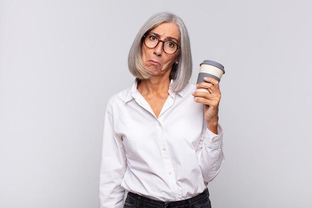 Женщина среднего возраста чувствует грусть и плаксивость с несчастным взглядом, плачет с негативным и разочарованным отношением к кофе.