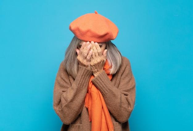 슬프고, 좌절하고, 긴장하고, 우울하고, 양손으로 얼굴을 가리고, 울고있는 중년 여성