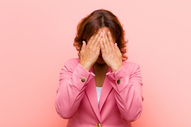 Middle age woman feeling sad, frustrated, nervous and depressed, covering face with both hands, crying against pink wall