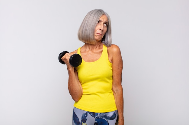 Middle age woman feeling sad, upset or angry and looking to the side with a negative attitude, frowning in disagreement. fitness concept