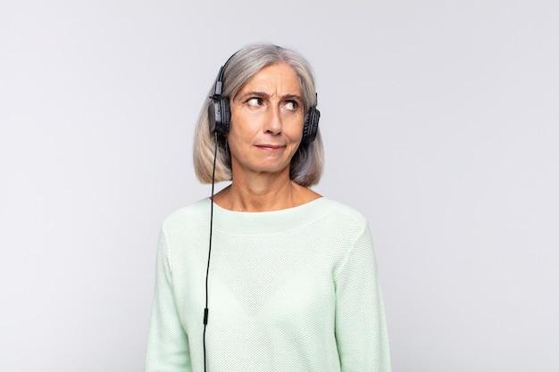 Женщина среднего возраста грустит, расстроена или злится, смотрит в сторону с отрицательным отношением и хмурится в знак несогласия. музыкальная концепция