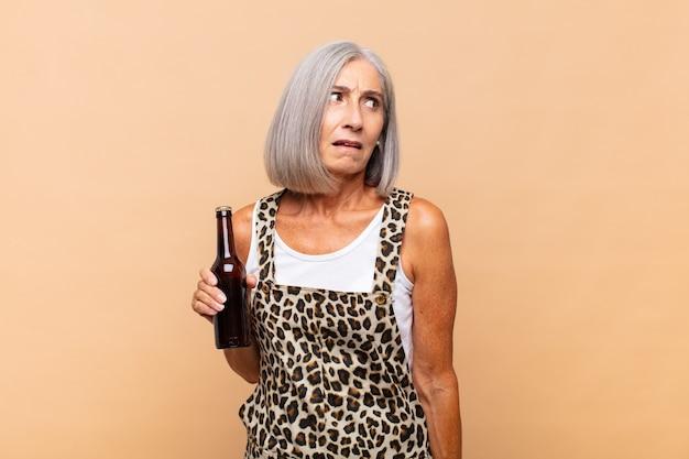 Женщина среднего возраста грустит, расстроена или злится и смотрит в сторону с негативным отношением, хмурясь, не соглашаясь с пивом
