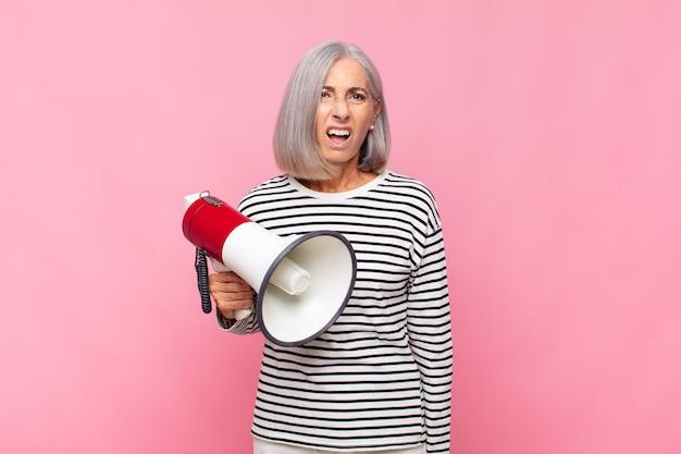 Женщина среднего возраста грустит, расстроена или злится и смотрит в сторону с отрицательным отношением, хмурясь, не соглашаясь с мегафоном
