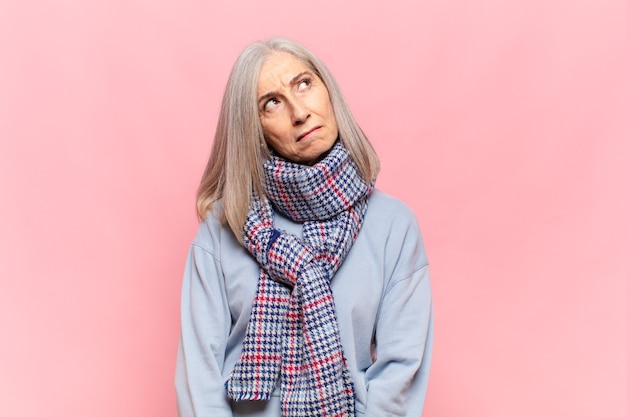 Женщина среднего возраста грустит, расстроена или злится и смотрит в сторону с негативным отношением, хмурясь в знак несогласия.