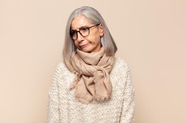 Женщина среднего возраста грустит, расстроена или злится, смотрит в сторону с негативным отношением и хмурится в знак несогласия.