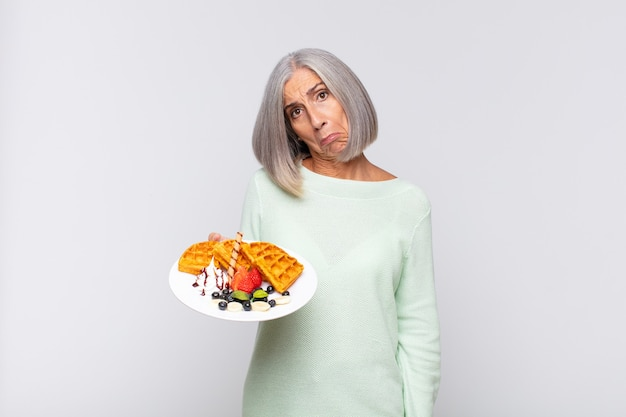 Middle age woman feeling sad and whiney with an unhappy look, crying with a negative and frustrated attitude. breakfast concept