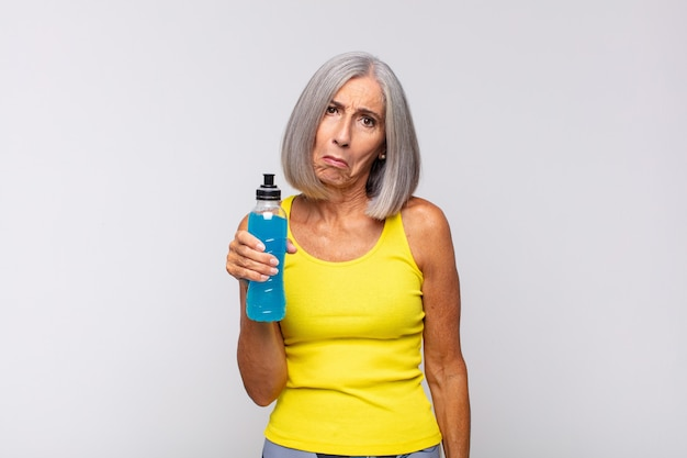 Middle age woman feeling sad and whiney with an unhappy look, crying with a negative and frustrated attitude. fitness concept
