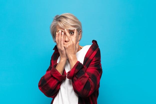 Женщина среднего возраста чувствует себя напуганной или смущенной, подглядывает или шпионит с полузакрытыми руками глазами