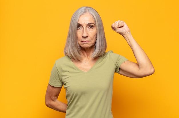 Женщина среднего возраста чувствует себя серьезной, сильной и мятежной, поднимает кулак, протестует или борется за революцию