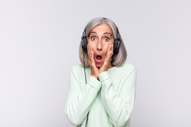 Женщина среднего возраста чувствует себя потрясенной и напуганной, выглядит испуганной с открытым ртом и руками по щекам. музыкальная концепция