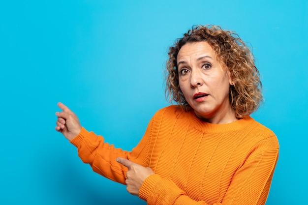 Женщина среднего возраста чувствует себя потрясенной и удивленной, указывая на скопированное пространство сбоку изумленным взглядом с открытым ртом