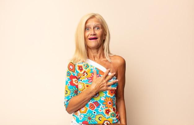 Женщина среднего возраста чувствует себя потрясенной и удивленной, улыбается, берет руку к сердцу, счастлива быть единственной или выражает благодарность