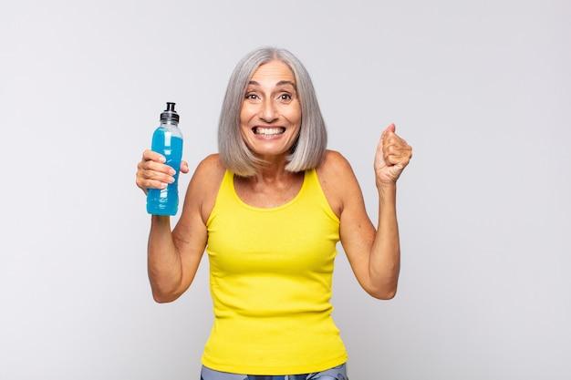 중년 여성은 충격, 흥분, 행복, 웃음과 성공 축하, 와우!. 피트니스 개념