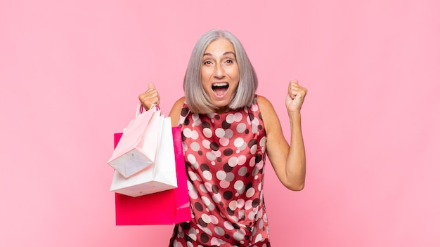 Женщина среднего возраста чувствует себя потрясенной, взволнованной и счастливой, смеется и празднует успех, говоря