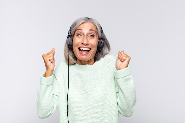 Middle age woman feeling shocked, excited and happy, laughing and celebrating success, saying wow!. music concept