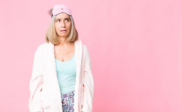 Женщина среднего возраста чувствует себя потрясенной, счастливой, изумленной и удивленной, глядя в сторону с открытым ртом. концепция ночного костюма