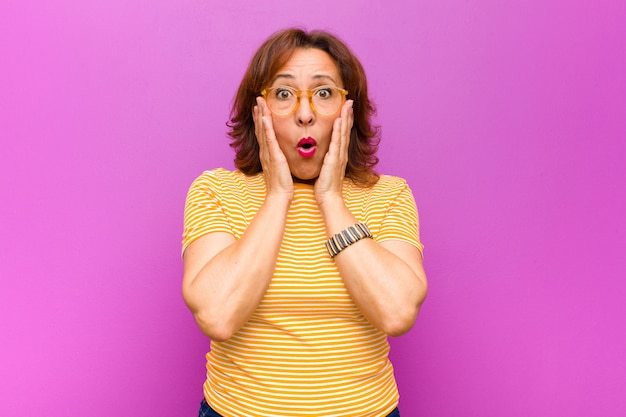 Middle age woman feeling shocked and scared, looking terrified with open mouth and hands on cheeks over purple wall