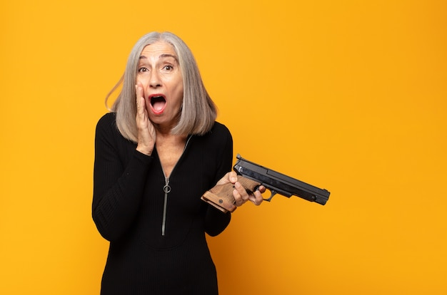 Middle age woman feeling shocked and scared, looking terrified with open mouth and hands on cheeks